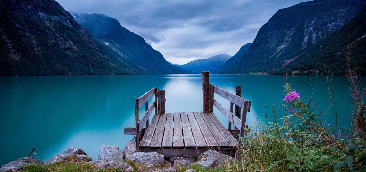 Beautiful image of blue water, mountain view, and a wooden platform.